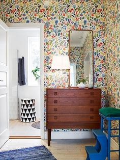 Pretty floral wallpaper with mid century furniture in this cute bedroom