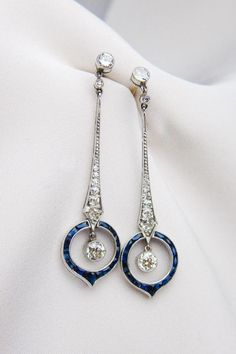Art Deco Sapphire & Diamond Earrings Circa These lovely platinum Art Deco Era earrings feature stunning sapphire and diamond dangles. Each earring is adorned with 15 calibre-cut natural sapphires weighing carats total. These sapphires encircle ro Bijoux Art Deco, Art Deco Jewelry, Fine Jewelry, Jewelry Design, Vintage Diamond Rings, Art Deco Diamond, Sapphire And Diamond Earrings, Diamond Jewelry, Diamante Art Deco