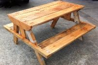 This picnic table was built from refurbished pallets that were originally used to carry bags of cement and aggregates, so the timber is quite sturdy. The timber was sanded just enough to get rid of splinters and rough spots, but not too much, as the final product is meant to be rustic. The design is bulkier than traditional picnic tables, as we mean for the product to last as long as possible in the elements. The table was finished off by applying oil with a slight amber stain.