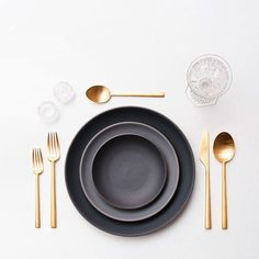 Unusal Table setting with golden cutlery & black/grey plates.