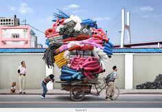 Tótems del consumismo: cargadores en Shanghái llevando a cuestas la desmesura de este sistema