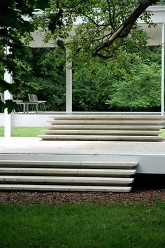 Stairs leading up from the ground via an intermediated terrace to the covered outdoor space of the house. The Farnsworth House by Mies van der Rohe (1945-1951).