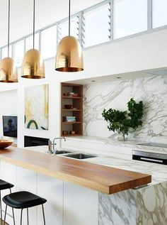 Modern kitchen with marble backsplash, wood cabinents, and gold pendant lights