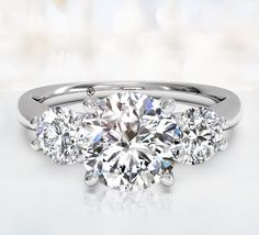 """The Knot"" Engagement Ring Trend #10 is three-stone settings are the perfect combination of sparkle and symbolism. Also known as trinity or trilogy rings, their three diamonds often represent the past"