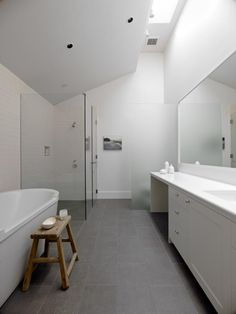 master The bathrooms all have the same hard-wearing porcelain tiles in different shades of gray. The tiles have an outdoor scale with dimensions of 12 by 24 inches and have the appearance of stone tiles.