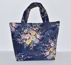 This handbag / small tote is made with an elegant navy blue and colourful floral print cotton fabric with a navy lining. There is one internal