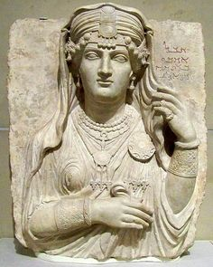 """Stele from Palmyria in the Roman province of Syria, about 200 CE  The Aramaic inscription is, """"Alas, Umm'abi, daughter of Maggi, son of Male, son of La'ad"""". The linear style of carving and the clothing and jewelry reflect local fashions. The sculpture was once painted: the jewely shows traces of red, blue, green, and yellow pigment."""