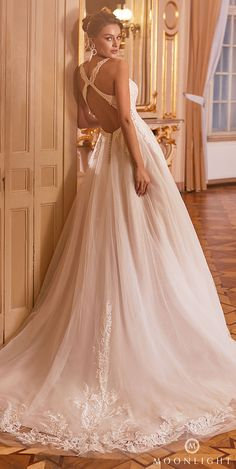 Ball gown wedding dress with halter neckline and lace bodice and tulle skirt | Romantic princess bridal dress with criss cross open back for a fairytale affair | Gilded X Moonlight Collection Fall 2021 Wedding Dresses - J6825 - Belle The Magazine | See more gorgeous bridal gowns by clicking on the photo