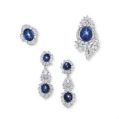 A SET OF STAR SAPPHIRE AND DIAMOND JEWELLERY Comprising a pendant/brooch, set to the centre with a cabochon star sapphire, within a foliate surround of marquise, brilliant and baguette-cut diamonds; and a ring and a pair of ear pendants en suite, mounted in 18k white gold