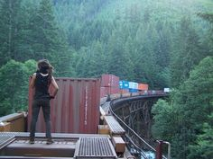 Awesome shot. Girl standing on top of shipping containers on a moving train.