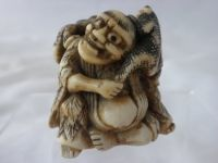 Antler netsuke with Gamma sennin. Good antler netsuke with a seated Gamma sennin, unusual one with 3 toads, eyes inlaid with horn. Flake on toe. Size 38mm high - 39mm wide. Late 18th early 19th C