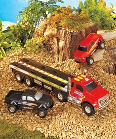 """Light & Sound Transporter Truck Set Make his playtime more exciting with the working lights and realistic sounds of the friction-powered Light & Sound Transporter Truck Set. The transporter itself is a Ford F-650 Super-duty truck, and it's hauling a Ford F-150 and a Chevy Silverado. The 1:24 scale trucks feature authentic details right down to the blazing decals on the sides. Plastic. 24-1/4"""" x 7"""" x 5"""". For ages 3 and up. Working lights! Realistic sounds! $13.95 set"""