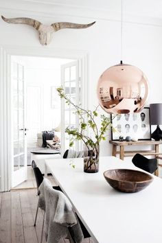 White on white interior with natural accents. Love the white dining table paired with black chairs, copper pendant light, greenery in the vase and sun-bleached bull skull over the door. Gorgeous floorboards and interesting art too!