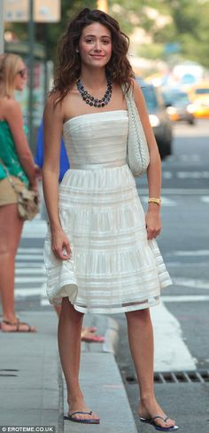 Emmy Rossum showed off her fashion credentials in a white strapless dress as she left her hotel in New York on Saturday