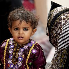 Bedouin child and mother - Oman   •   If I remember correctly, many cultures throughout the Middle East will ring their infant and toddlers eyes with kohl in order to keep away evil spirits.