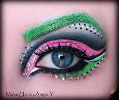Pink crystals accent dramatic pink and black eye shadow with a green glitter brow.