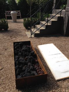 raw steel frame filled with oversize black lava rocks. S Ceasar Stone top will cover the firepit in warmer months to be used as a coffee table. Amazing house!!