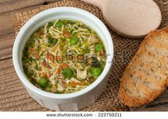 Soup with pasta and vegetables on old wooden table - stock photo