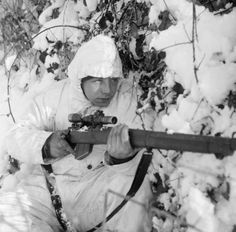 A sniper of the 6th Airborne Division, wearing his snow camouflage suit, on patrol in the Ardennes/14 January 1945.