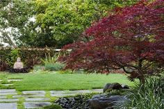 This soothing Asian landscape has so many of the classic elements - Buddha statue, Japanese maple - yet doesn't feel cliched since the designer incorporated so many fresh types of foliage and used modern ways with hardscape. Design by AJ Shepard of Ca. Read more Asian landscape design tips here: http://www.landscapingnetwork.com/garden-styles/asian.html