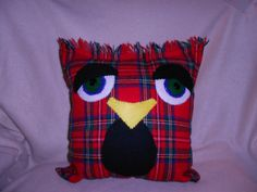 """Roger is an owl pillow I made up from an old red plaid skirt. He measures 12"""" square-not including his fringe. :)  His body is red, black, white, yellow and blue plaid.  I made his eyelids and chest from scraps of black polyester/cotton pants.  His eyes are made from white, blue and green felt with black button centers.  His beak is a scrap of yellow felt.  His body is machine sewn on 3 sides. All other sewing is done by hand.I do not have shape cutter, so every element of his face has been…"""