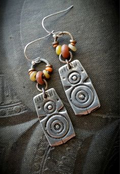 Stunning silver tribal charms dangle below aged rings attached to rusty hoops with added Indonesian glass all the way around, finished off with sterling silver ear wires.  •very light weight •100% artisan hand made •Yucca Bloom Original♥