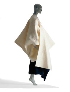 This coat from Rei Kawakubo's 1983-1984 Autumn/Winter collection for Comme des Garcons is made of wool felt. Though it has a strong, sculptural form when worn, it's actually made of two panels, the smaller of which slides through a slit in the larger piece and hangs from the side of the chest. There are no buttons or fasteners.