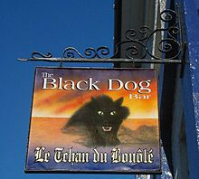Pub sign in English and Jerriais.  The montrous black dog is said to haunt Bouley Bay in Trinity Parrish.