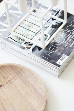 elisabeth heier white framed lantern box on magazine stack white table wooden