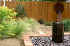 An Albuquerque, NM take on a zen garden. Love the granite water feature and flowing grasses. Design by Erin's Gardens of New Mexico.