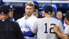Toronto Blue Jays' Justin Smoak eyes down New York Yankees Chase Headley (12) during a bench-clearing melee after Yankees pitcher Luis Severino charged Smoak after hitting him with a pitch during second inning American League baseball action, in Toronto on Monday, Sept.26, 2016. THE CANADIAN PRESS/Frank Gunn