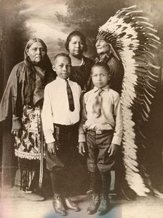 Back row L-R: Tatatty (Comanche) with her niece, Wifeper or Frances Wright (Comanche/African American), and Tatatty's husband, Tatenequer (Comanche) Front row L-R: Henry Wright (Comanche/African American) son of Frances Wright, and his brother, Lorenzano Wright (Comanche/African American) - circa 1910