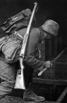 German soldier searching a house with a wooden stick. In this very well preserved print, the Kar Karabiner 98K, Cal. 8×57-IS rifle carried b...