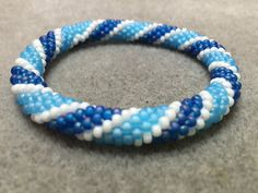 Matte blues striped with white.  This beautiful beaded bangle just slips over your hand.  See photos for other colours it has been made in.  Also