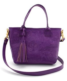 "Add some southwest charm to your day with this tooled leather handbag. Constructed from a sturdy purple leather that features a stunning tooled floral pattern. A leather interior lining, matching interior pocket, magnetic closure, 14"" strap, and removable matching leather tassel makes this a great day to day bag. Measures 13"" x 8"" x 4"". This purse is versatile as it pairs well with jeans and your favorite tee, or with a dress and statement jewelry."
