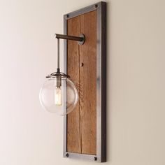 Check out Umanoff Rectangular Industrial Sconce - Small from Shades of Light This oversized tall wall sconce is hand crafted in Richmond, Virginia by independent lighting designer Wendy Umanoff, and is the perfect melding of rustic chic with rugged industrial style. Darkened raw steel is used to frame the rustic reclaimed wood panel with exposed industrial bolts in each corner for added strength and durability. The single exposed light bulb is suspended from a hanging rod and enclosed in a…