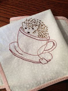 a little hedgehog in a teacup that I embroidered on a hanky for a friend