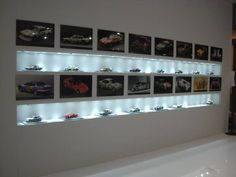 Cool idea for Alex's toy room- metal models displayed with pictures of the actual car. Great lighting enhance the die cast models.