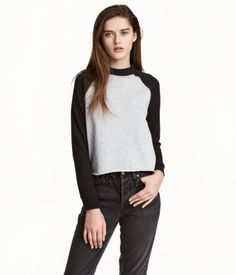 Black. Short sweatshirt with contrasting raglan sleeves, ribbing at neckline and cuffs, and cut-off, raw-edge hem.