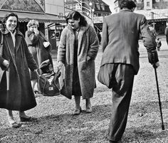 "Two women carry a so-called ""GI baby"" in a sportsbag as a man with one leg passes by on crutches.  Scene from 1950's post war Germany by GI Bill Perimutter"