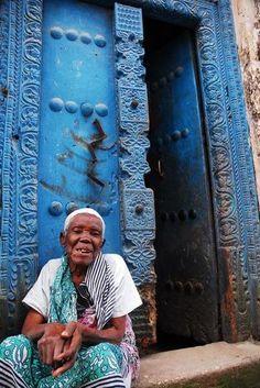 Old woman in front of blue door · Stone Town, Zanzibar