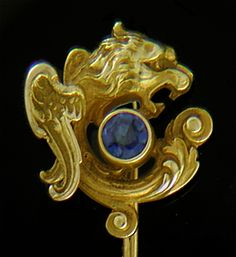 The Victorians loved small jewels populated with fantastic and mythological creatures.  This beautifully sculpted stickpin features a winged lion-serpent fiercely guarding a bright blue sapphire.  The tail of the lion-serpent flows beneath the sapphire with elegant scrolls and acanthus leaves.  Beautifully crafted in 14kt gold,  circa 1900.