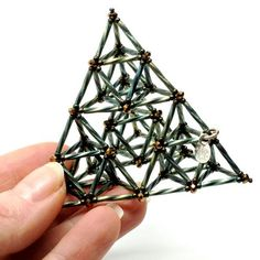 One of my signature pieces of beadwork, this large beaded bead is a study in the symmetry of a tetrahedron, a pyramid with a triangular base. It is composed of 4 medium sized tetrahedrons, each of which is composed of 4 tiny tetrahedrons, for a total of 16 tiny tetrahedrons. This particular arrangement is known as a second generation Sierpinski tetrahedron, named after Waclaw Sierpinski. Waclaw Sierpinski was a 20th century Polish mathematician who pioneered the field of fractal geometry…