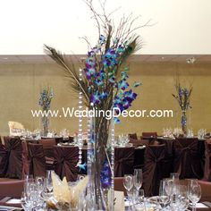 Wedding Centerpiece - natural birch branches, blue dendrobium orchids, peacock feathers and hanging crystals in a tall sqaure glass vase