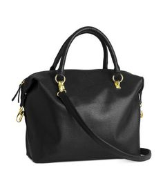 Soft handbag in imitation leather. Double handles, top zip, and detachable shoulder strap. Three inner compartments, one with zip. Lined. Size 10 1/2 x 12 1/4 in.