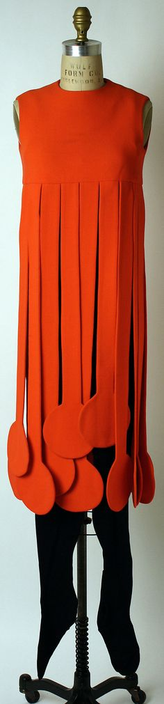 Ensemble by Pierre Cardin, French, 1971. Orange wool dress with long fringed skirt and sleeveless black bodysuit worn with black leather pumps.