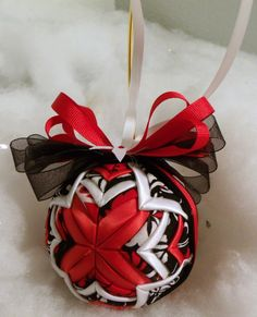 "Black, Red, and White Cathedral handmade quilted ornament:    This 3"" handmade quilted ornament is made with red satin, white satin ribbons and layered with black, red, and white fabrics. It is layered in the cathedral pattern. The final quilted ornament, not including the bow and ribbon loop, measures approximately three inches in diameter. This ornament would look charming in your favorite bowl or basket or as a decoration in a room. It will make a great Christmas tree decoration! It makes ..."
