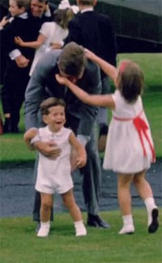 President John F. Kennedy being greeted by his children on the White House lawn.