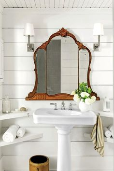 Charming shiplap bathroom with shaded sconces, vintage tri-fold mirror and pedestal sink.