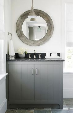 Stunning charcoal gray paneled bathroom vanity is fitted with polished nickel pulls and topped with black marble countertops holding a round sink and a polished nickel faucet.